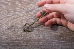 Hand die een retro gestileerde decoratieve sleutel houden stock foto