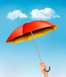 Hand die een rode en gele paraplu houden tegen een blauwe hemel Royalty-vrije Stock Afbeeldingen