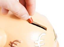Hand die een rode pil in een spaarvarken, concept voor sparen geld opnemen Royalty-vrije Stock Afbeelding