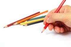Hand die een rood potlood houdt Stock Foto's