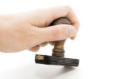 Hand die een rubberzegel houdt Stock Foto