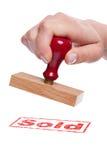 Hand die een rubberzegel met het Verkochte woord houdt Royalty-vrije Stock Afbeeldingen
