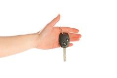 Hand die een sleutel geeft die op wit wordt geïsoleerde Stock Foto's