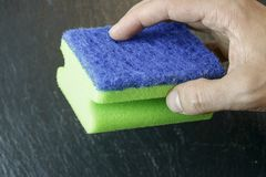 Hand die een spons houdt stock afbeelding