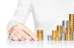 Hand die een stapel muntstukken toevoegt aan besparingen Stock Afbeeldingen