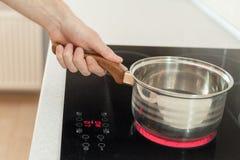 Hand die een steelpan in moderne keuken met inductiefornuis houden royalty-vrije stock fotografie