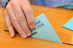 Hand die een stemmingsstemming in een groef van doos zet Stock Afbeelding