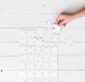 Hand die een stuk van wit onafgewerkt raadsel houden Stock Afbeelding