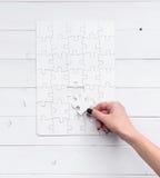 Hand die een stuk van wit onafgewerkt raadsel houden Royalty-vrije Stock Foto