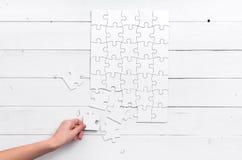 Hand die een stuk van wit onafgewerkt raadsel houden Royalty-vrije Stock Fotografie