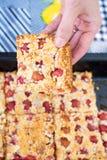 Hand die een stuk van zoete eigengemaakte kersenpastei nemen met kruimeltaart Stock Afbeelding