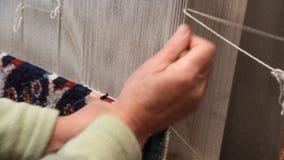 Hand die een tapijt knopen stock footage