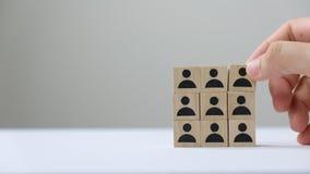 Hand die een team bouwen door houten de mensenpictogram van het kubusblok te zetten stock video