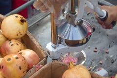 Hand die een vers granaatappelsap drukken stock afbeeldingen