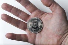 Hand die een zilveren bitcoin op een witte achtergrond houden Royalty-vrije Stock Foto