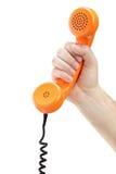 Hand, die ein altes orange Telefongefäß anhält lizenzfreie stockfotos
