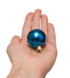 Hand, die ein blaues Weihnachtsspielzeug anhält Stockfoto