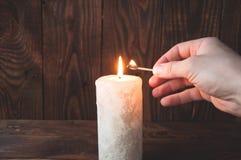 Hand, die ein brennendes Match und Lichter ein Kerze h?lt lizenzfreie stockfotos