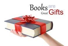 Hand, die ein Buch für Geschenk hält Lizenzfreies Stockbild