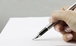 Hand, die ein Dokument unterzeichnet lizenzfreies stockfoto