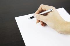 Hand, die ein Dokument unterzeichnet lizenzfreie stockbilder