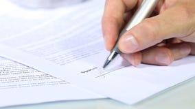 Hand, die ein Dokument, Unterzeichnungskonzept unterzeichnet stock video footage