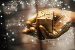 Hand, die ein Geschenk anhält Stockfotos