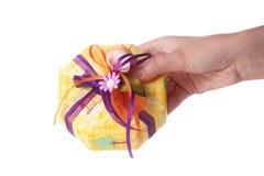 Hand, die ein Geschenk gibt Stockfotografie