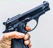 Hand, die ein Gewehrschießenkonzept hält stockfotos