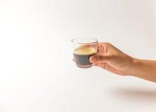 Hand, die ein Glas Espressokaffee hält Lizenzfreie Stockfotografie