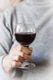 Hand, die ein Glas Rotwein anhält stockfotografie
