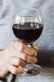 Hand, die ein Glas Rotwein anhält lizenzfreie stockfotos