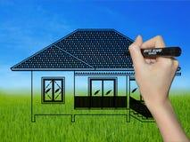 Hand, die ein Haus auf einer Landschaft zeichnet Stockfotografie