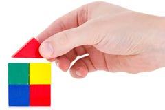 Hand, die ein Haus unter Verwendung der Holzklötze baut Stockfotografie