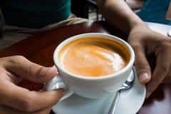 Hand, die ein heißes Getränkdesign des Tasse Kaffees hält Stockbild