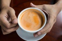 Hand, die ein heißes Getränkdesign des Tasse Kaffees hält Stockfoto