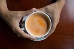 Hand, die ein heißes Getränkdesign des Tasse Kaffees hält Lizenzfreie Stockfotografie