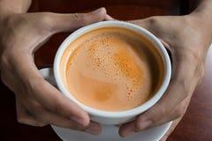 Hand, die ein heißes Getränkdesign des Tasse Kaffees hält Stockfotografie