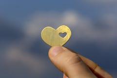 Hand, die ein Herz gegen den blauen Himmel hält Stockfoto