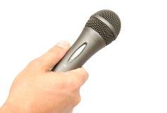 Hand, die ein Mikrofon anhält Stockbild