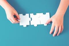 Hand, die ein Puzzlestück hält stockfotos