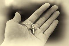 Hand, die ein silbernes Kreuz hält christentum Lizenzfreie Stockfotografie