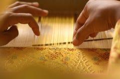 Hand, die ein Songket spinnt Stockbilder