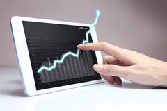 Hand, die ein steigendes Diagramm auf Tablette zeigt Lizenzfreie Stockbilder