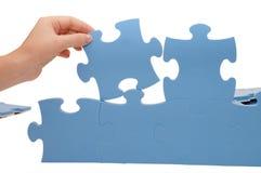Hand, die ein Teil eines Puzzlespiels montiert Stockfotografie