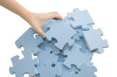 Hand, die ein Teil eines Puzzlespiels montiert Lizenzfreie Stockbilder