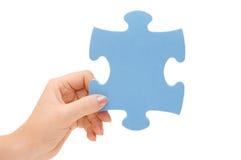 Hand, die ein Teil eines Puzzlespiels montiert Lizenzfreies Stockbild