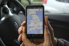 Hand, die ein Telefon, eine Karte zeigend hält Lizenzfreie Stockfotografie