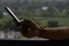 Hand, die ein Telefon mit unscharfem Hintergrund hält lizenzfreie stockbilder