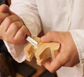 Hand, die ein Tier vom Stück Holz schnitzt Lizenzfreies Stockfoto